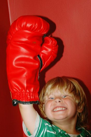 Portrait of cheerful boy wearing boxing glove against wall at home