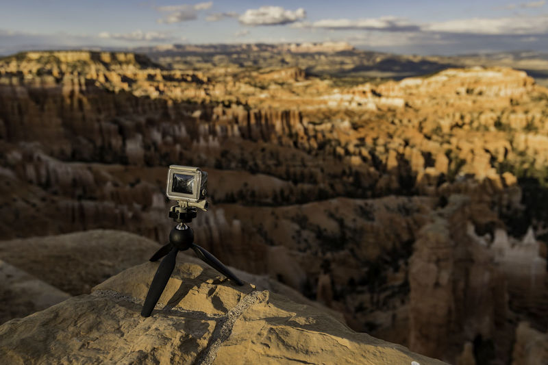 Close-Up Of Camera On Rock Against Canyon