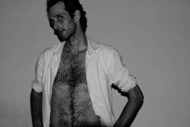 Portrait Of Man With Fully Unbuttoned Shirt Against Wall
