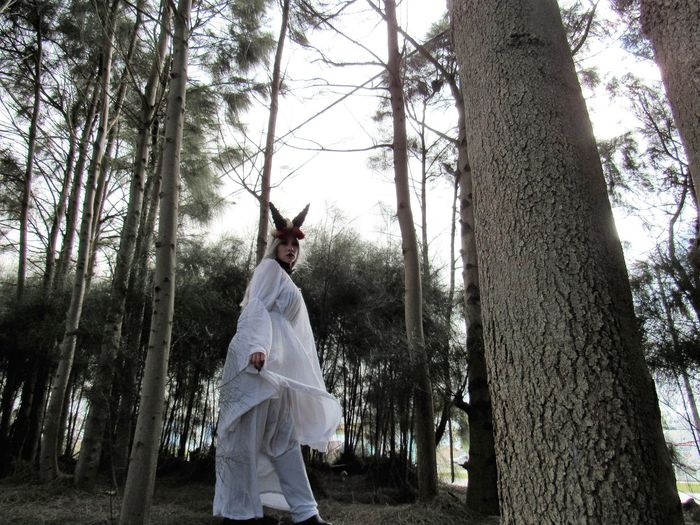 Woman Wearing Costume Standing Against Trees In Forest