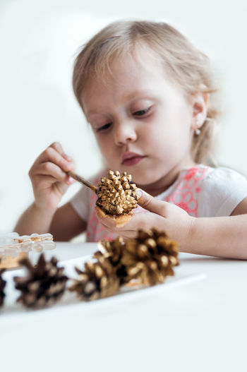 Close-up of girl painting pine cone on table