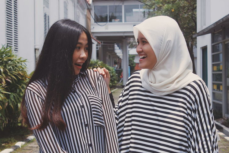 Happy female friends talking while standing against buildings