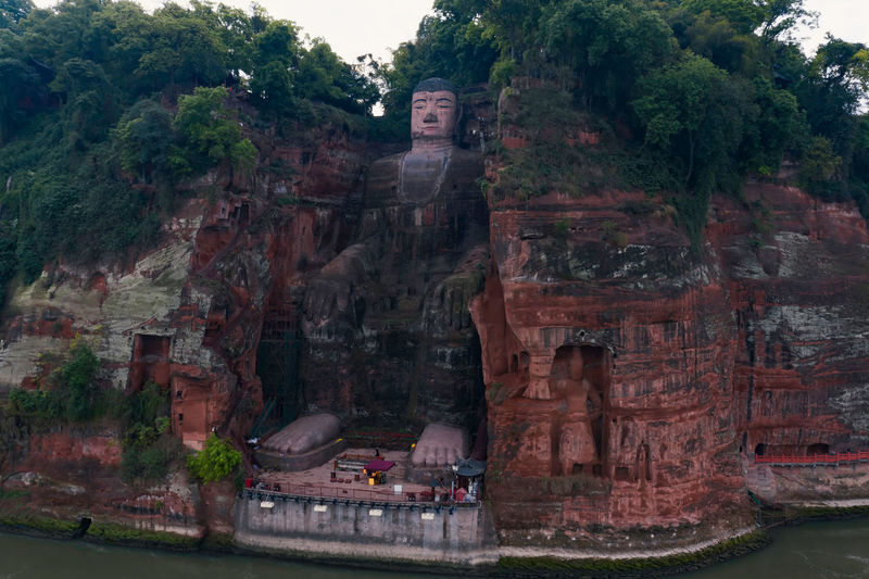 Leshan Giant Buddha China Sichuan Leshan Giant Buddha Buddha Buddha Statue Statue Art River Water Travel Travel Destinations Architecture Mountain Rock - Object Belief Religion Tree Tree Day Place Of Worship History Building Exterior The Past Nature Nature Beauty In Nature Building Plant Spirituality Sculpture No People Outdoors Aerial View