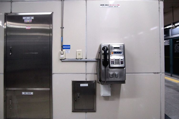 Pay phone mounted on wall at subway station