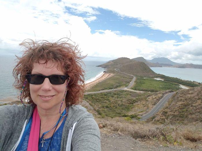 Portrait of smiling woman wearing sunglasses against landscape