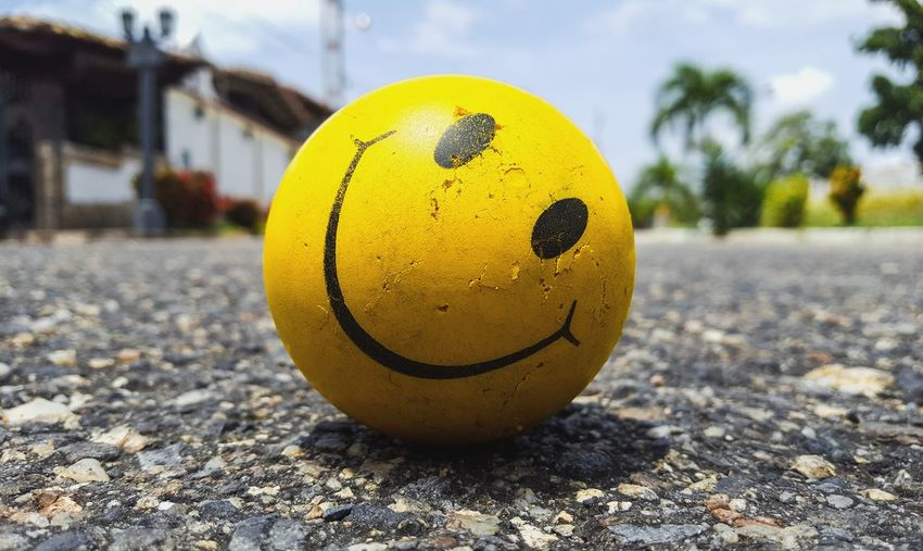 Close-up of smiley face ball on road
