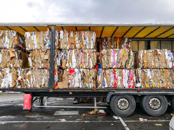 Stack of garbage on street against sky