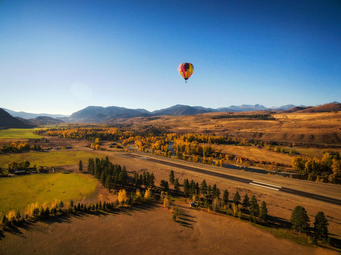 Hot Air Balloon Coming In For a Landing. A hot air balloon near the town of Winthrop in the Methow Valley comes in to land on a smoke jumpers airfield during a lovely autumn morning. Sky Hot Air Balloon Balloon Environment Nature Transportation Landscape Scenics - Nature Clear Sky Mid-air Flying No People Land Travel Outdoors Autumn Winthrop, WA Methow Valley Colorful Fall Valley Landing Countryside Drone Photography Aerial View