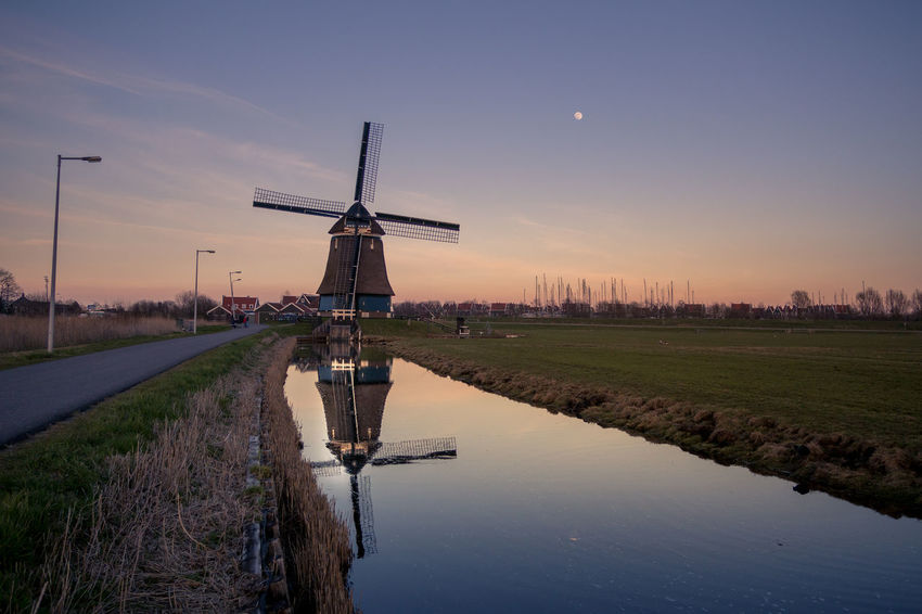 Alternative Energy Beauty In Nature Canal Environment Environmental Conservation Field Fuel And Power Generation Landscape Nature No People Reflection Renewable Energy Scenics - Nature Sky Sunset Tranquility Turbine Water Wind Power Wind Turbine