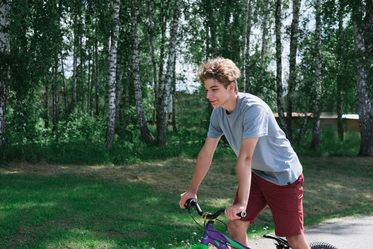 Teenager boy riding a bike in a park. curly teenager on a bicycle. active sport outdoors.