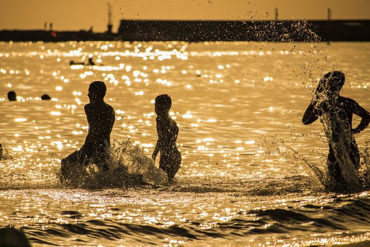 Children enjoying in sea during sunset