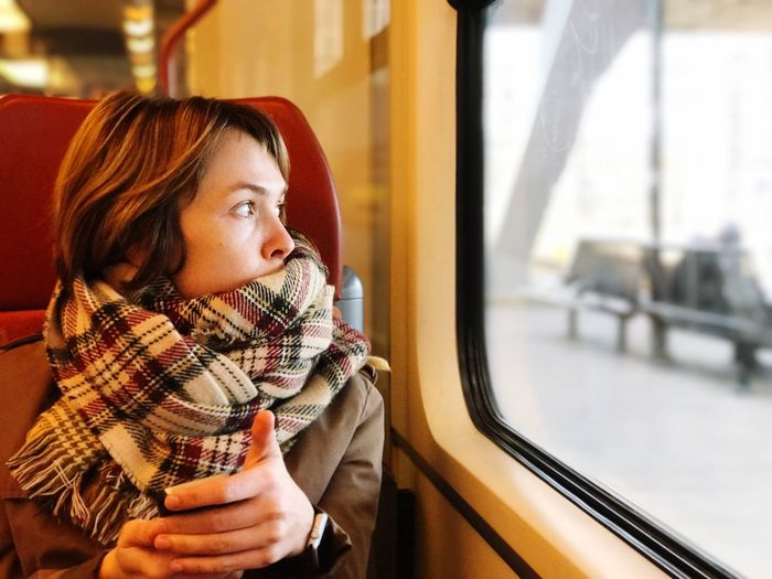 Mid adult woman looking through window while sitting in train