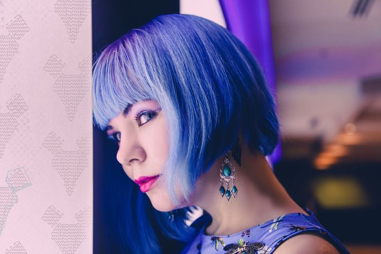 Side View Of Young Woman With Blue Hair Looking Away While Standing By Door