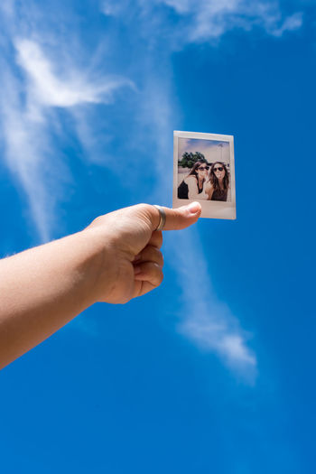 Cropped hand of person holding photograph against blue sky during sunny day