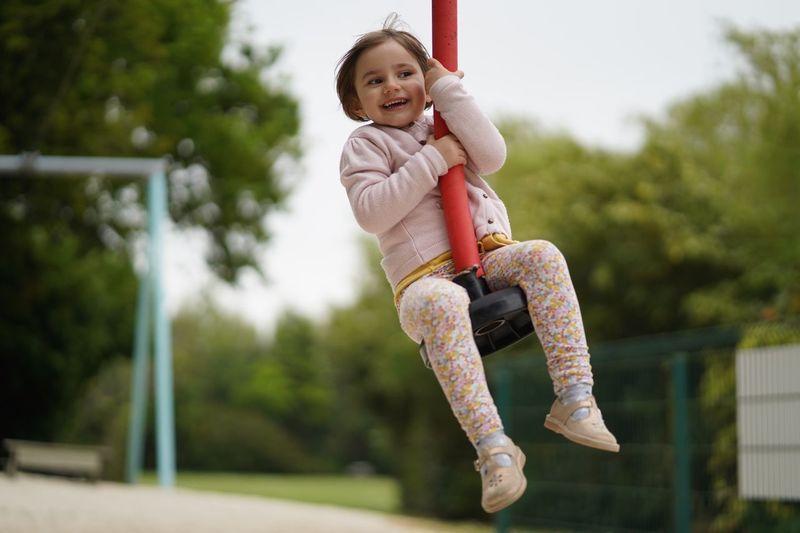 Happy Girl Sitting On Ride At Playground