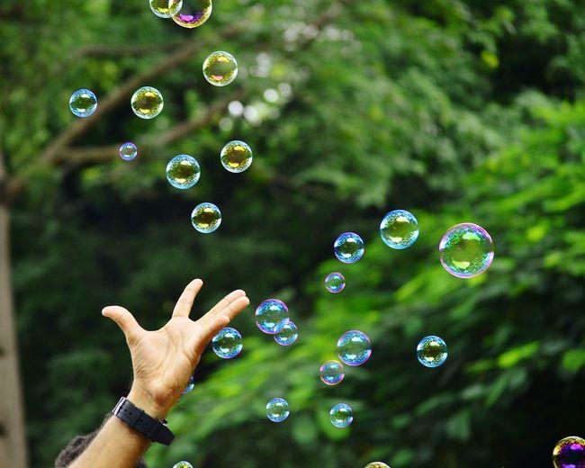 Close-up hand amidst bubbles