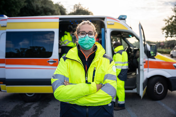 Portrait of doctor wearing mask standing against ambulance