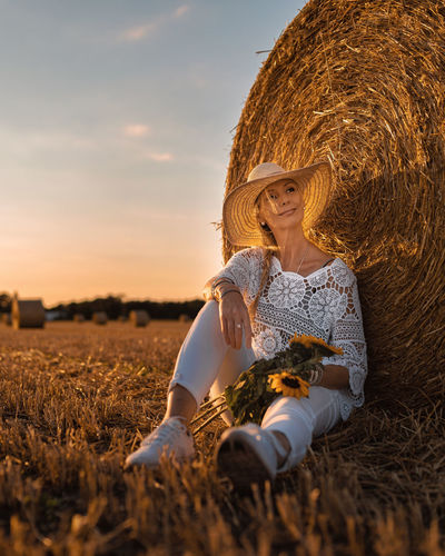 Woman wearing straw hat sitting on field