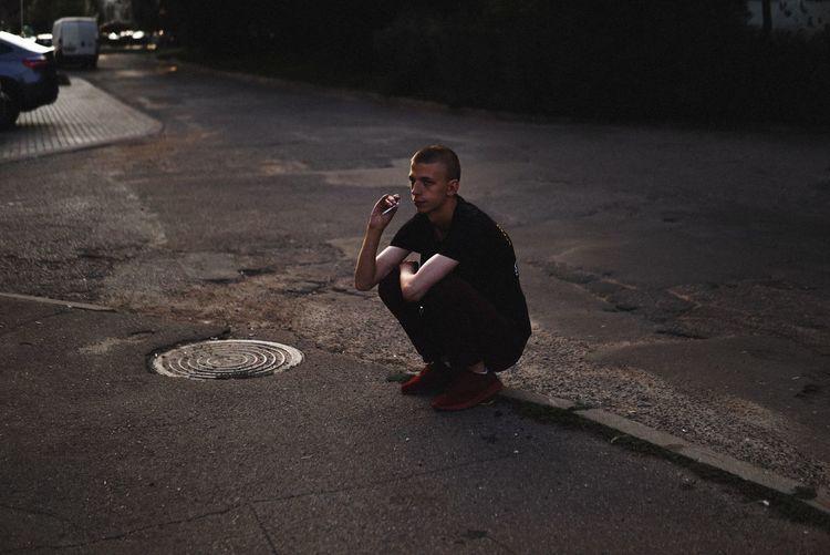 Man smoking cigarette while crouching on city street