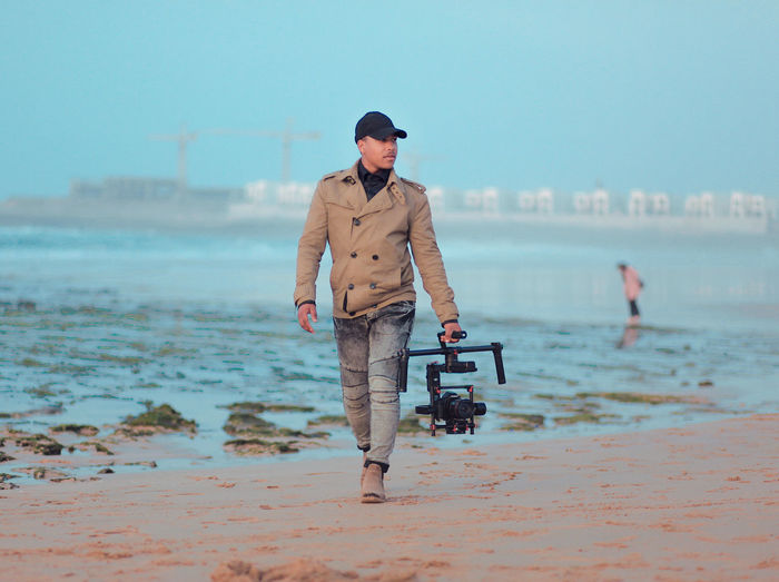 Full length of man holding camera while walking at beach
