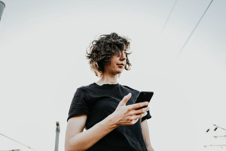 Young woman using mobile phone against clear sky