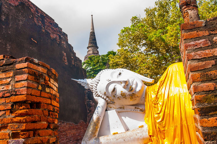 Wat Yai Chai Mongkhon Temple in Phra Nakhon Si Ayutthaya Historical Park With a white Buddha statue covered with a yellow robe, posing amidst the ancient ruins in Phra Nakhon Si Ayutthaya, Thailand. Ancient Architecture Art ASIA Asian  Ayutthaya Beautiful Brick Buddha Buddhism Buddhist Chai City Culture Day Face Heritage Historic Historical History Holy Landmark Monastery Mongkhon Mongkol Mongkon Old Outdoor People Reclining Religion Religious  Sculpture Site Sky Sleeping Statue Stone Temple Thai Thailand Tourism Travel Unesco Wat White World Worship Yai Yellow Belief Spirituality Built Structure Place Of Worship Building Building Exterior The Past Travel Destinations Representation Human Representation Male Likeness No People Outdoors The Traveler - 2019 EyeEm Awards