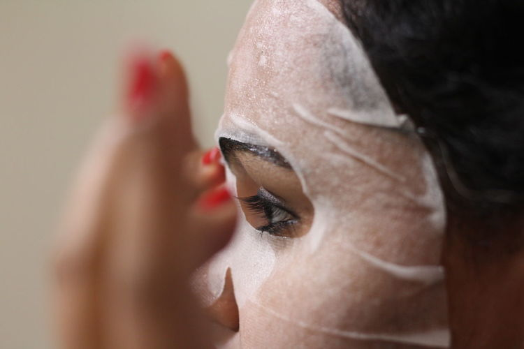 Close-up of woman using facial mask at home
