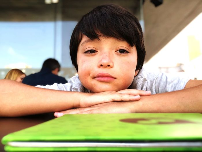 Close-Up Portrait Of Boy Leaning On Table