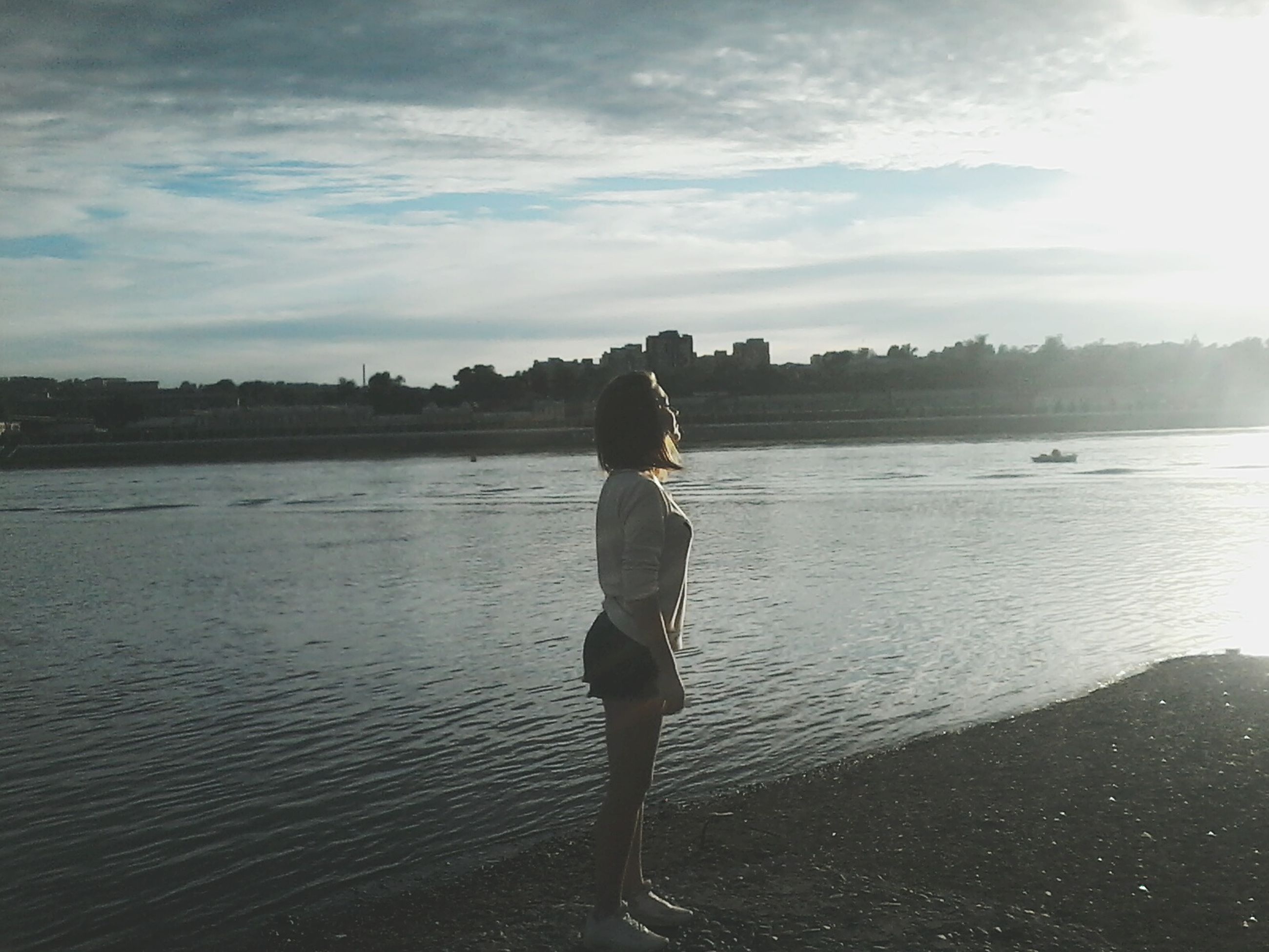 water, sky, full length, rear view, lifestyles, standing, leisure activity, casual clothing, sea, tranquility, cloud - sky, nature, walking, tranquil scene, person, lake, beauty in nature, river