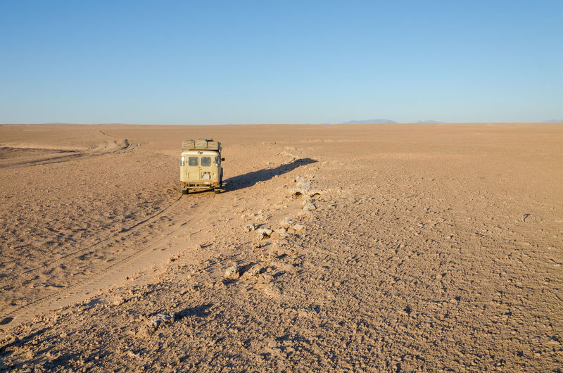 Vintage offroad car driving through empty namib desert of angola, africa