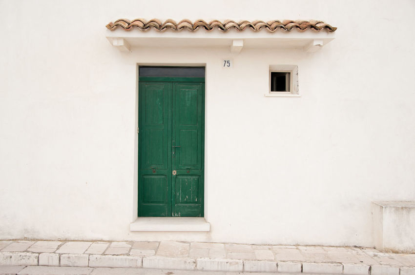 """In the old centre of Termoli, a medieval fort conceals a warren of narrow streets and heavily reinforced stone houses, including """"Number 75"""" with the green door. Architecture Green Color Historical Building Home Mediterranean  Termoli  Building Exterior Built Structure Centre Focus Day Door Doorway Green Door Historical House Italy Medieval Minimalism Molise No People Outdoors Plain Small Window Stone Wall Colour Your Horizn"""