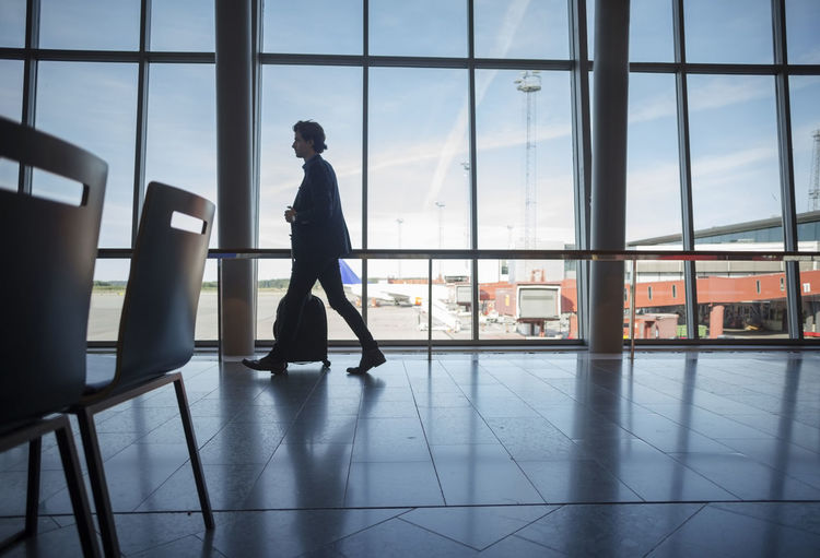 Side view of man standing at airport