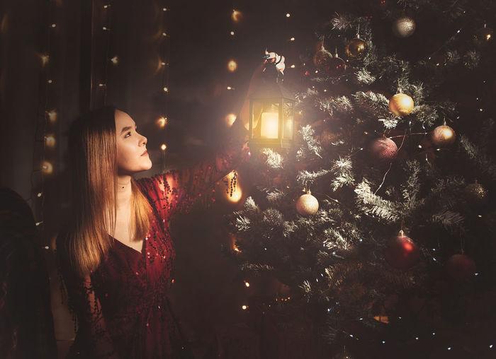 Woman looking at illuminated christmas tree at night