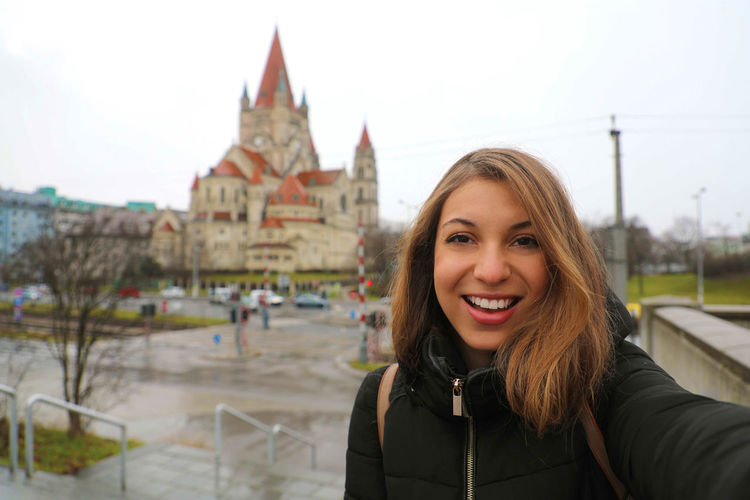 Young woman in Vienna, Austria Portrait One Person Smiling Looking At Camera Architecture Real People Happiness Young Women Young Adult Built Structure Leisure Activity Lifestyles Headshot Hair Building Exterior Emotion Front View Standing Hairstyle Warm Clothing Outdoors Mexicoplatz The Peterskirche (St. Peters Church) The Peterskirche (St. Peters Church) Vienna, Austria Girl