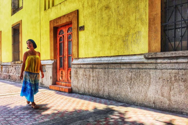 Full length rear view of woman walking on street against building