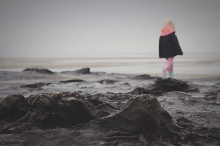 Girl walking by submerged tree stumps at beach