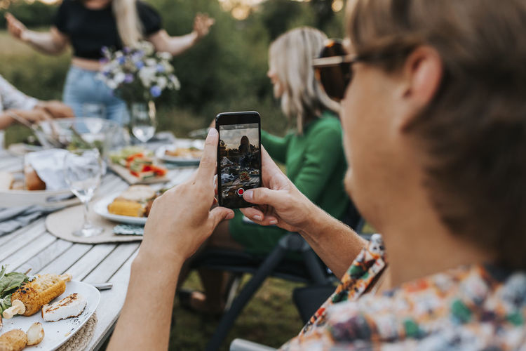Woman photographing with mobile phone on table
