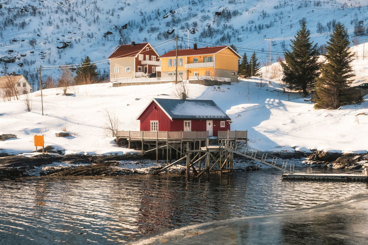 Houses by river amidst buildings during winter