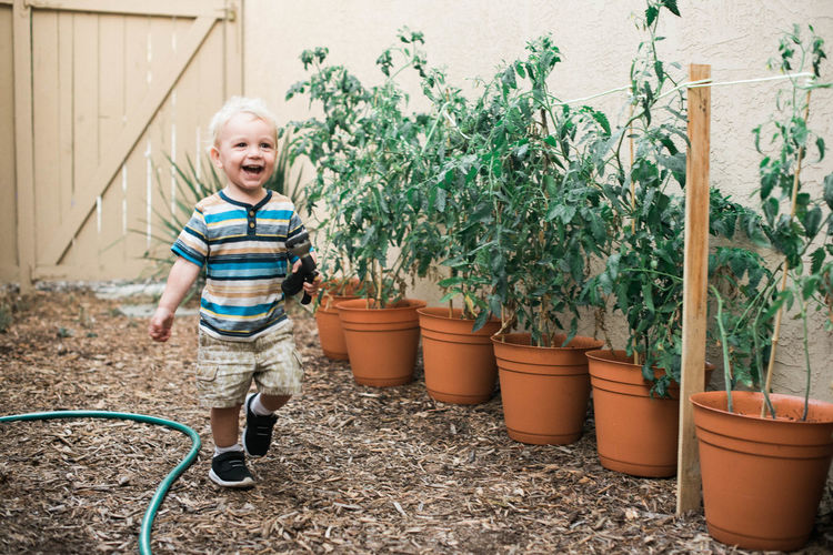 Happy boy and potted plants in yard
