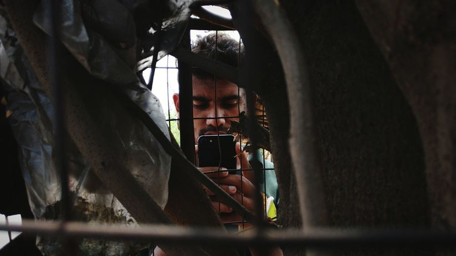 Close-Up Of Man Photographing Seen Through Fence