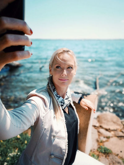 Portrait of smiling young woman taking selfie in front of sea