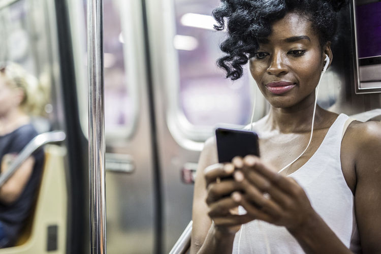 Portrait of woman using mobile phone while train