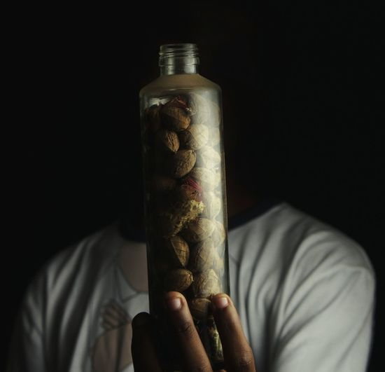 Close-up of man holding walnuts in bottle against black background