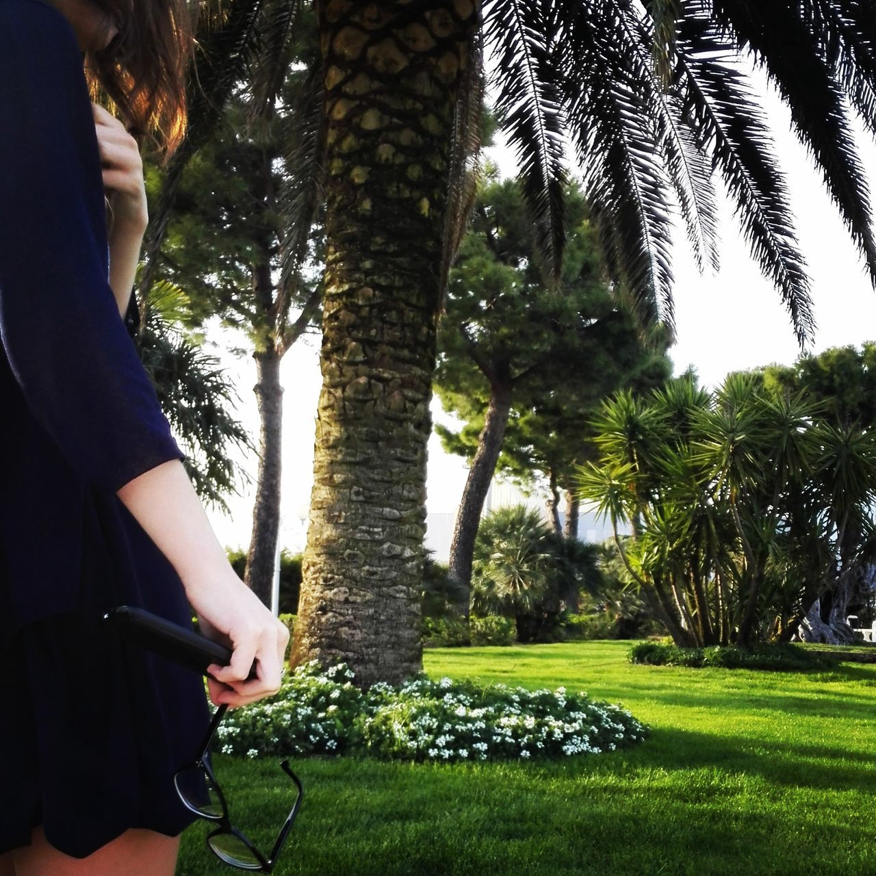 tree, one person, real people, tree trunk, lifestyles, day, leisure activity, growth, green color, nature, grass, women, outdoors, sitting, young women, young adult, standing, wireless technology, branch, beauty in nature, adult, people