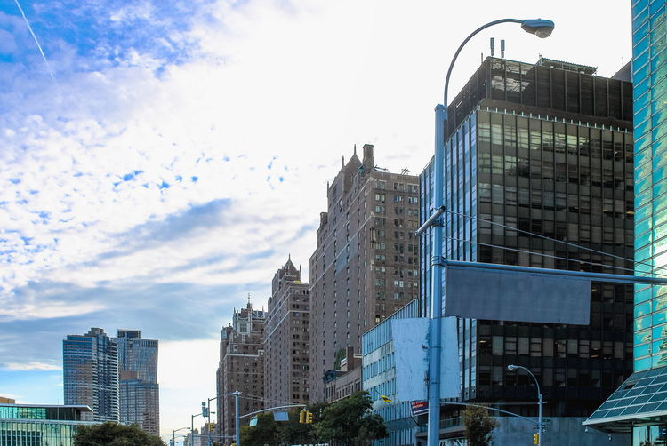 New York, USA - 26 September 2016: Buildings lining First Avenue looking toward lower Manhattan from 44th Street outside the One UN Plaza building. 1st Avenue Manhattan New York USA America Architecture Building Exterior Built Structure City Cityscape Cloud - Sky Day First Avenue Low Angle View Modern No People Outdoors Sky Skyscraper Urban Skyline