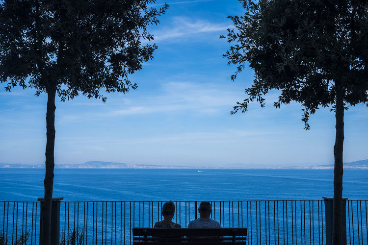 landscape of Naples gulf and mediterranean sea view from a senior couple sitting on a bench Bench Mediterranean Sea Relaxing Sitting Beauty In Nature Blue Cloud - Sky Couple - Relationship Leisure Activity Lifestyles Men Nature Outdoors Plant Real People Rear View Scenics - Nature Sitting Sky Togetherness Tranquil Scene Tree Two People Water Women