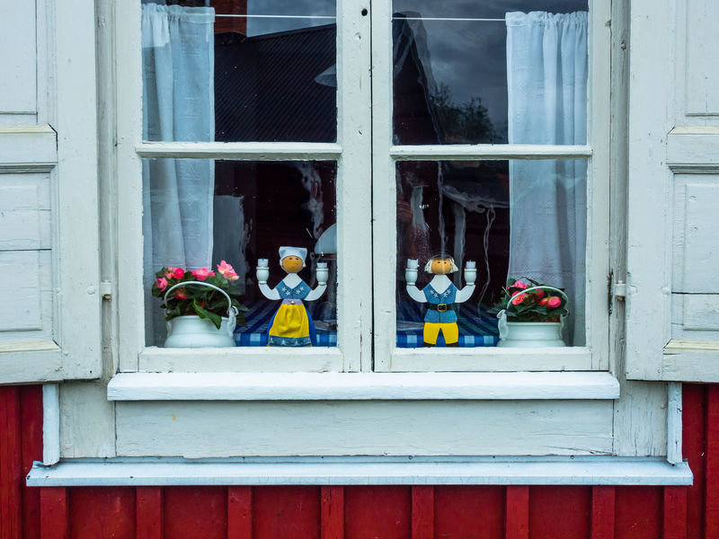 Closed window with wooden figures in national dress EyeEmNewHere Window Architecture Built Structure Building Exterior Glass - Material Day Building Outdoors No People Clothing Reflection Transparent Red Togetherness Window Frame Sweden National Dress Wooden Figure Decoration Museum