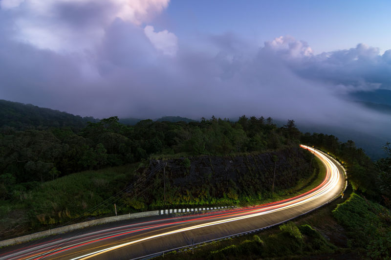 Beautiful road on the way up to inthanon national park at dusk, fog in the forest. long exposure.