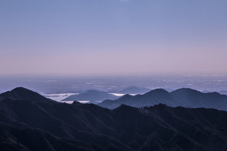 Scenic view of mountains against clear sky at dusk
