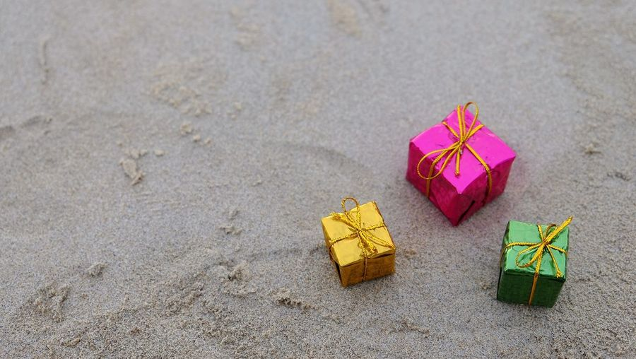 High angle view of gifts on sand